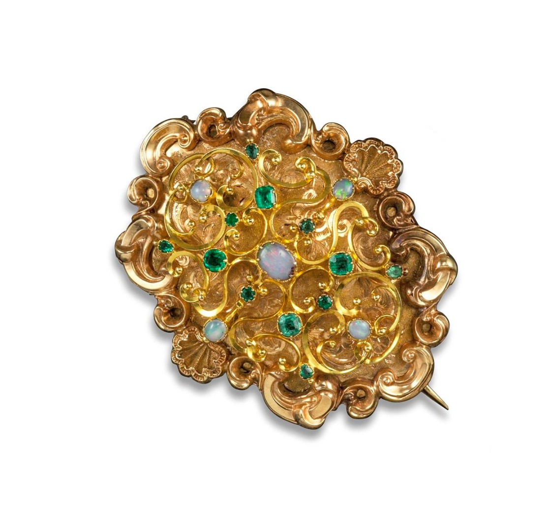 A Victorian gem-set gold brooch. Set with opals and emeralds on an openwork...