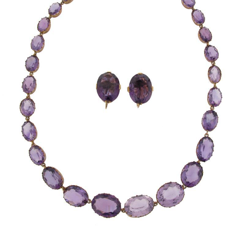 A Victorian graduated oval shaped amethyst riviere necklace. Gilt metal cut...
